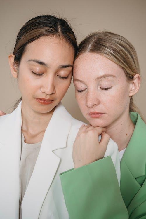 Woman in Green Blazer Hugging Woman in White Blazer