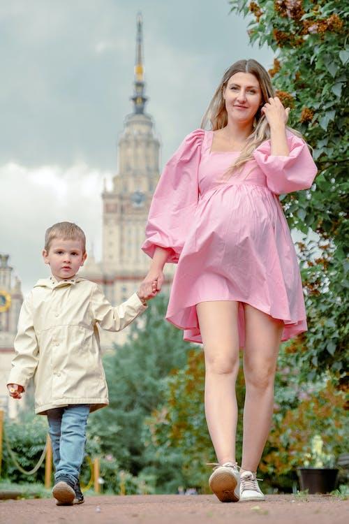 Girl in Pink Dress Holding Girl in White Dress