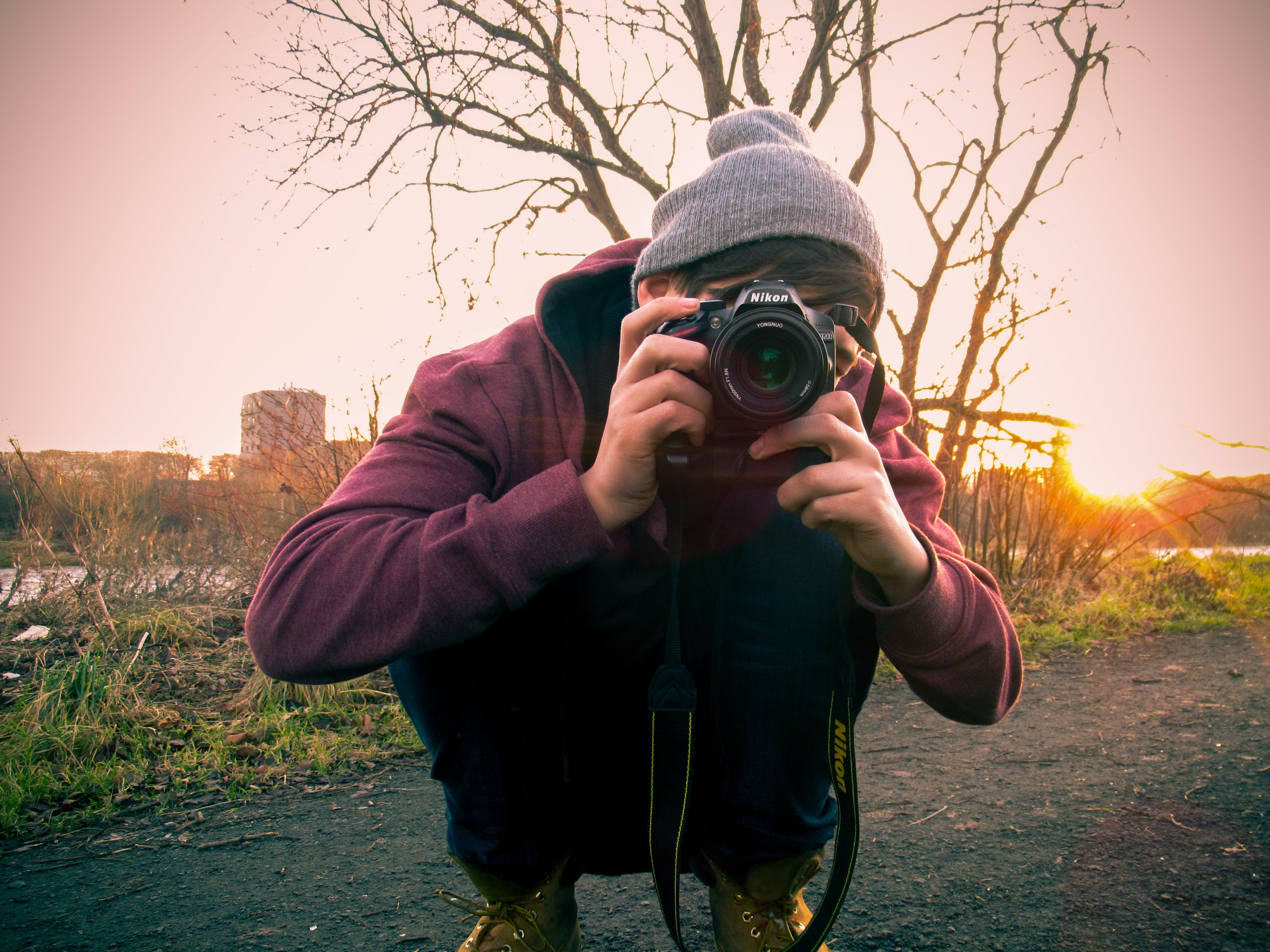 Man in Red Jacket Holding Black Dslr Camera