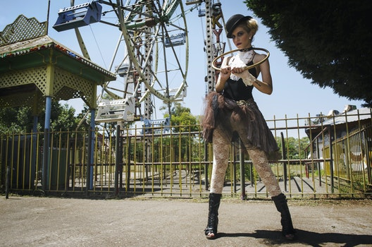 Woman in Black Camisole Top Stands Behind Ferris Wheel