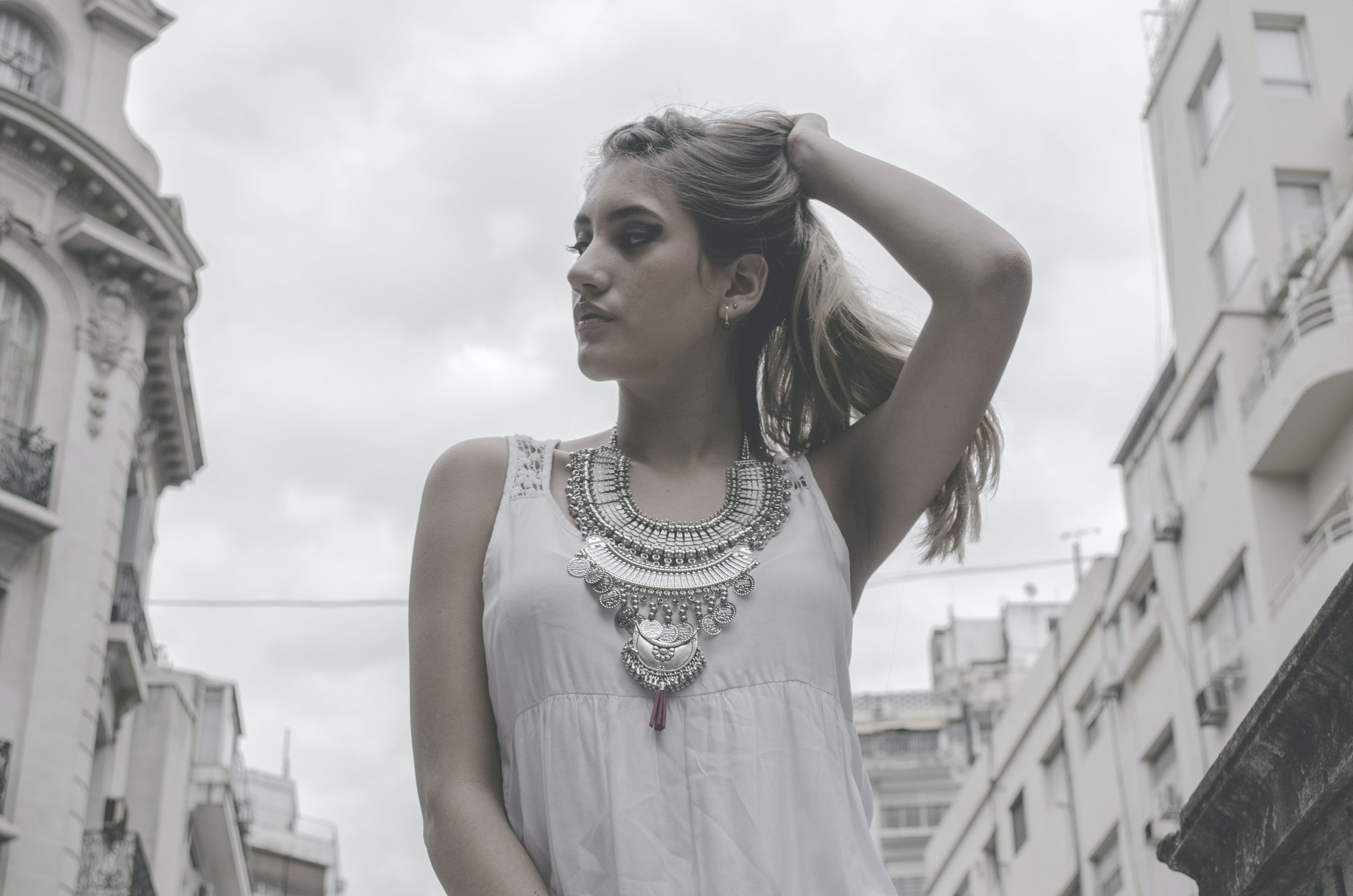 Woman Wearing White Tank Top Holding Hair Pose