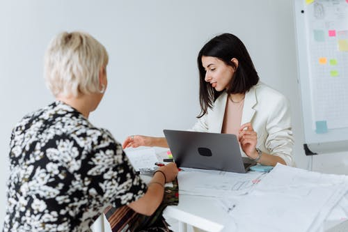 Woman in White Blazer using Laptop