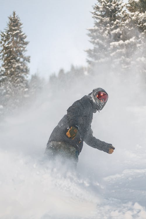 Person in Grey Jacket and Red Snow Goggles Riding on Snowboard