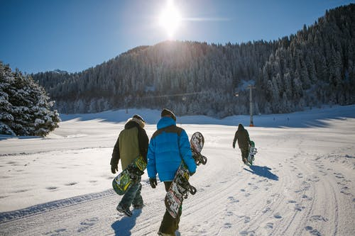 Three Person Holding Bubble Jacket Carrying Snowboards