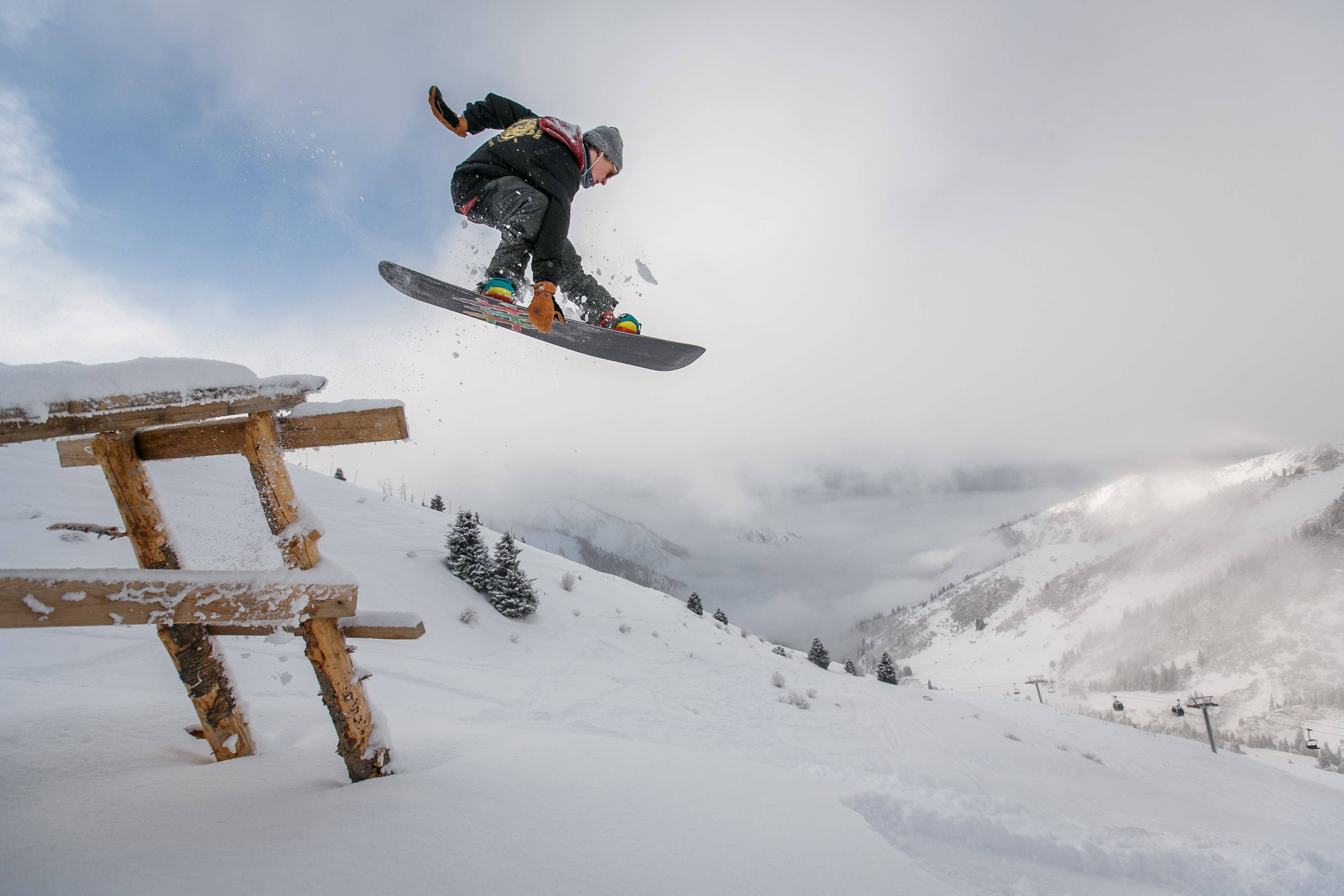 Man in Black Snowboard With Binding Performs a Jump