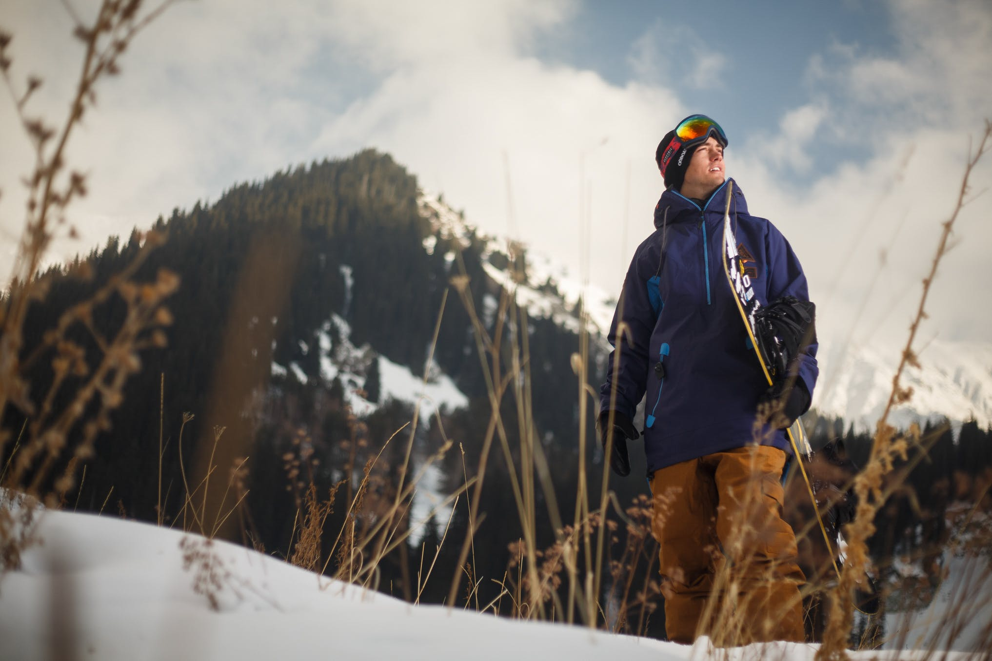 Low Angle Photography of Man Wearing Blue Jacket Carrying Snow Board
