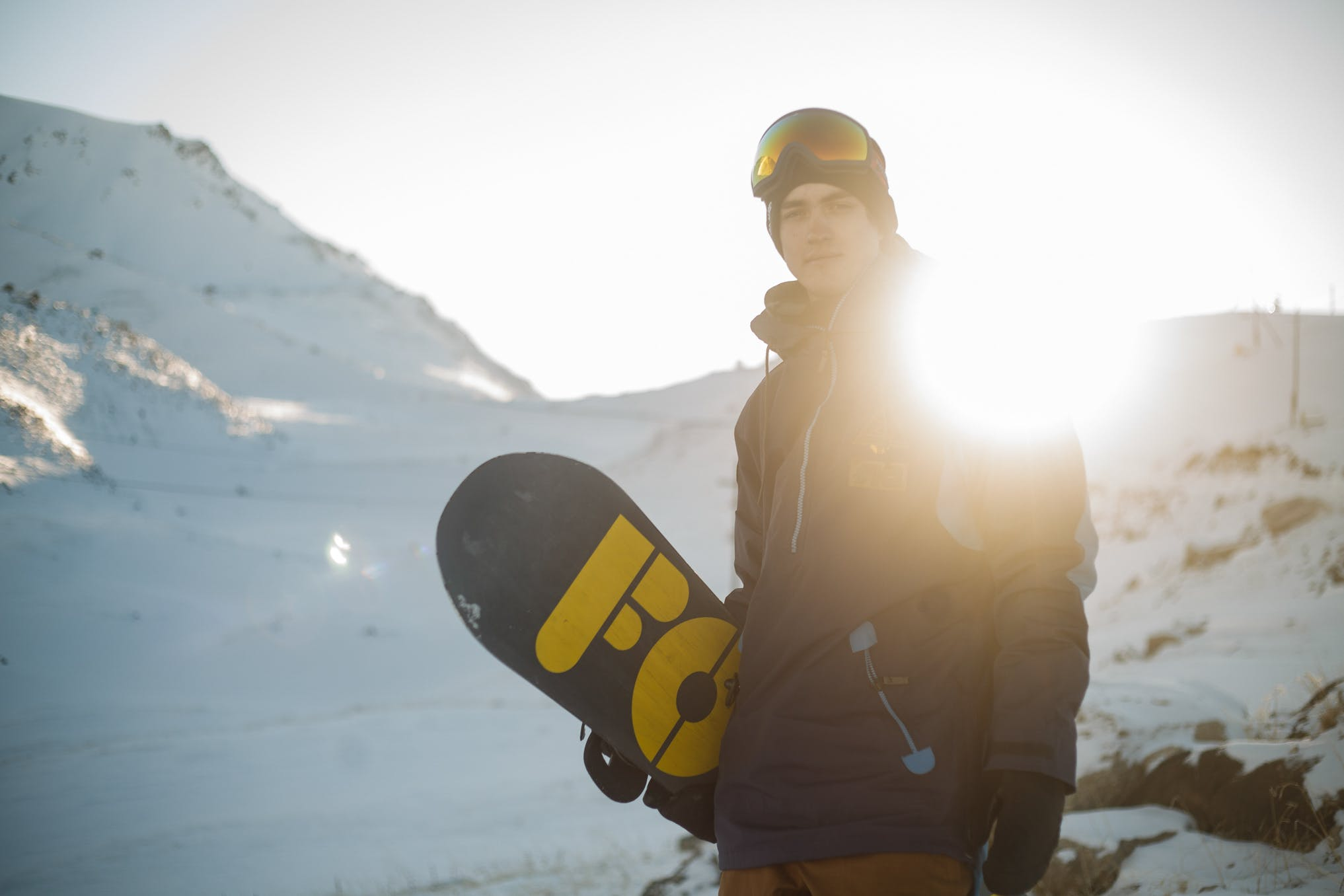 Man in Blue Pullover Hoodie Holding Blue and Yellow Snowboard