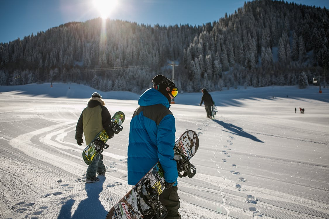 Person Wearing Blue Winter Jacket Carrying Snowboard Under Sunny Sky