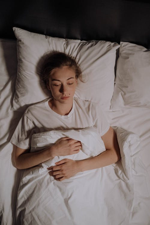 Woman in White Shirt Lying on Bed