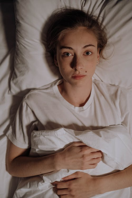 Woman in White Shirt Lying Down on White Bed Sheet