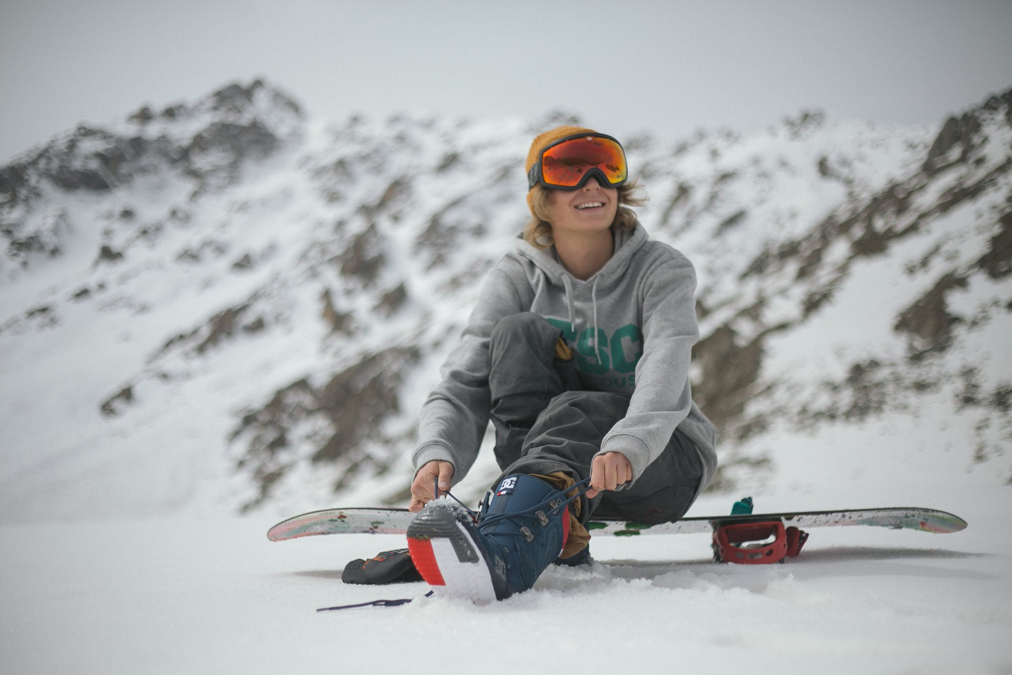 Person in Grey Hoodie Sitting on Snowboard