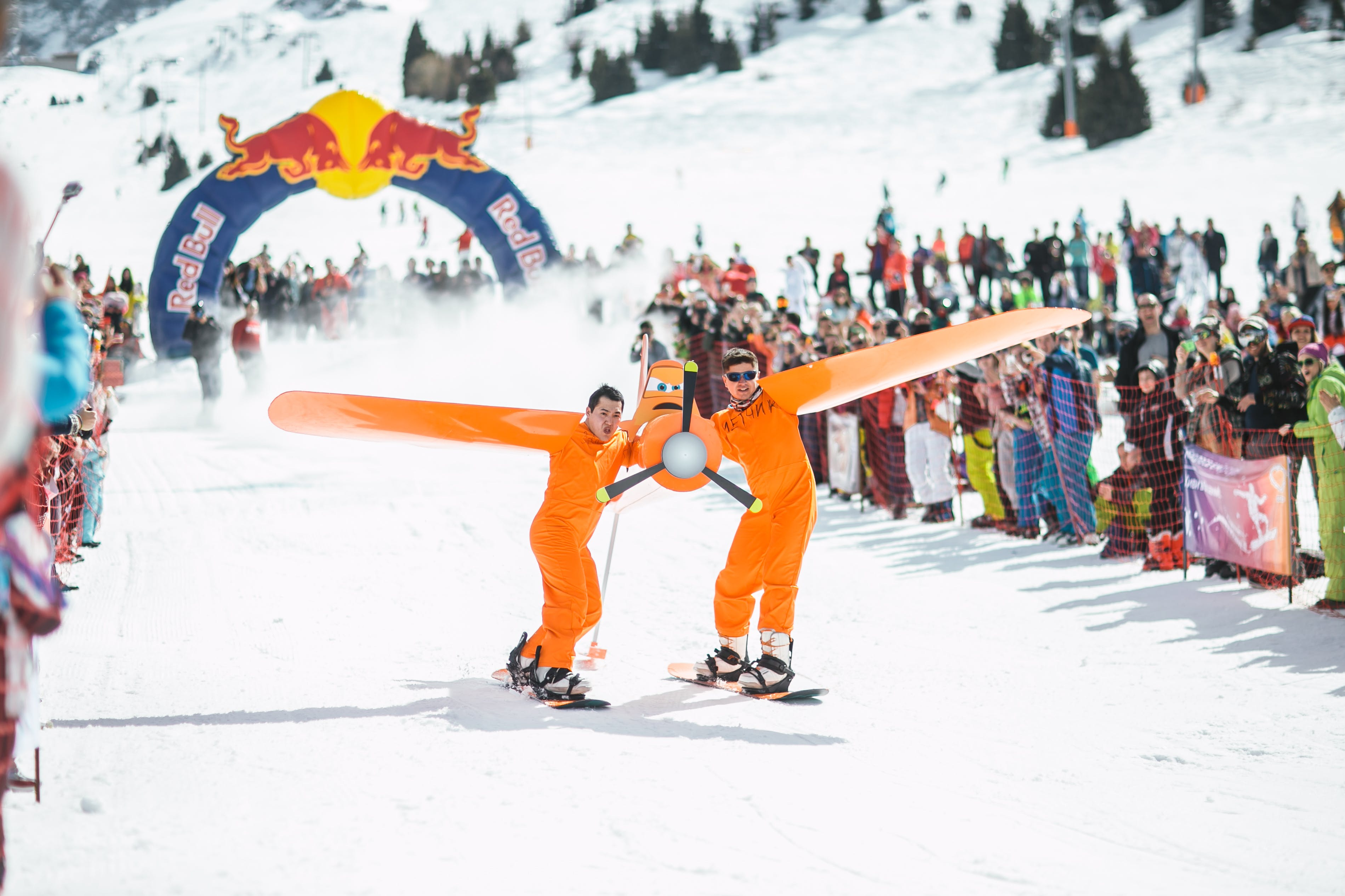 Photography of Men in Orange Suits Ridding Snowboard