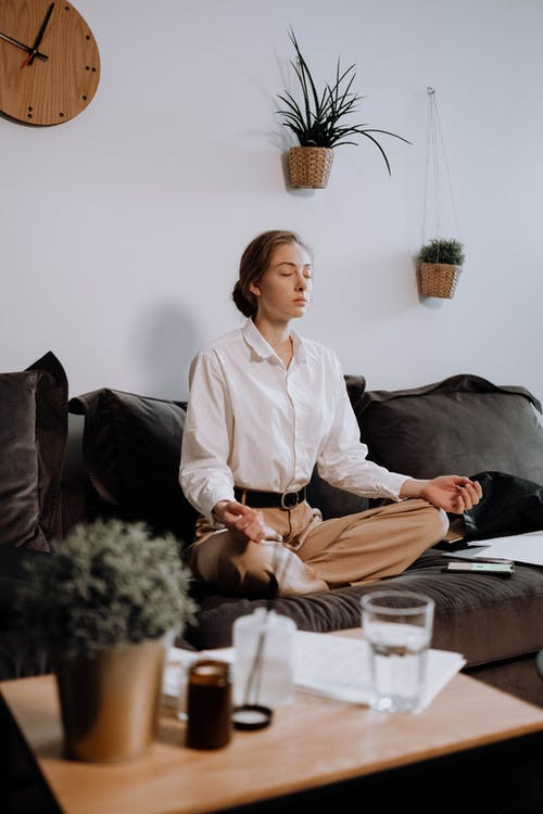 Woman in White Button Up Long Sleeve Shirt Sitting on Black Couch In Lotus Position