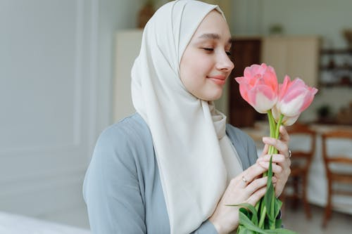 Close-Up Photo of a Woman in Hijab Holding Pink Flowers