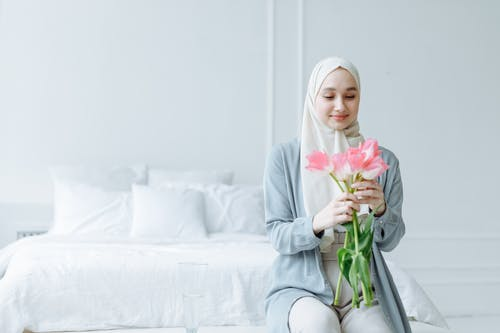 Woman in White Hijab Looking at the Fresh Pink Roses