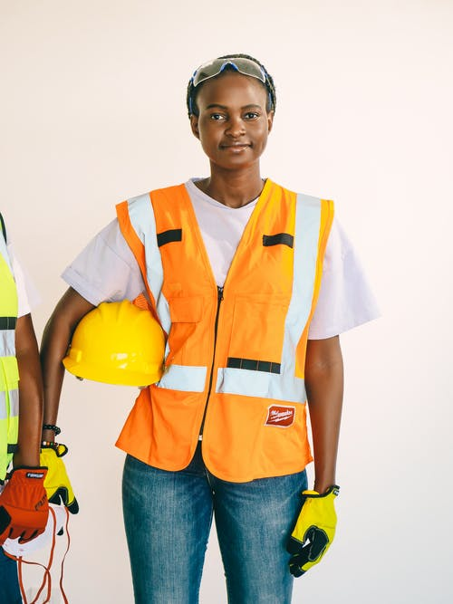 Boy in Yellow and Orange Vest Holding Yellow Hard Hat