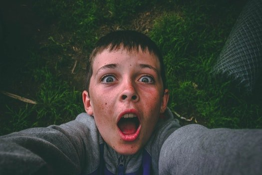 Opened Mouth Black Haired Boy in Gray Full-zip Jacket Standing on Grass Field Taking Selfie