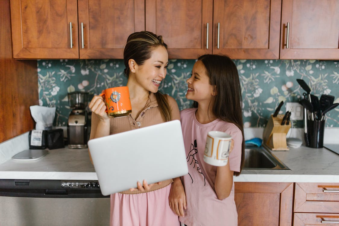 Mother and Daughter Smiling while Looking at Each Other Holding Mugs