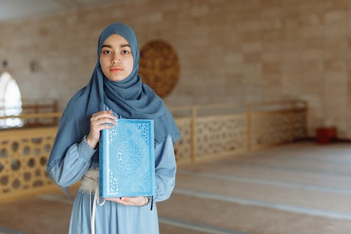 Woman in Blue Hijab Holding Blue Book