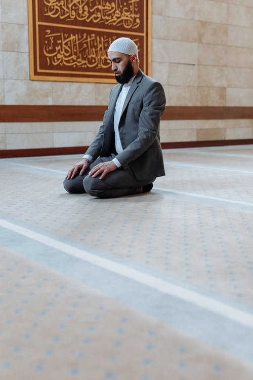 Man in Black Suit Sitting on Floor