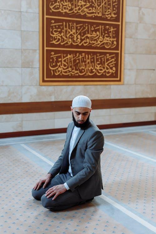 Man in Gray Coat Kneeling on Floor