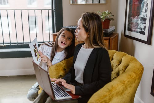 A Daughter Showing Her Artwork while Her Mother is Using a Laptop