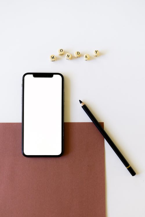 Close-Up Shot of a Mobile Phone beside a Black Pencil on a White Surface