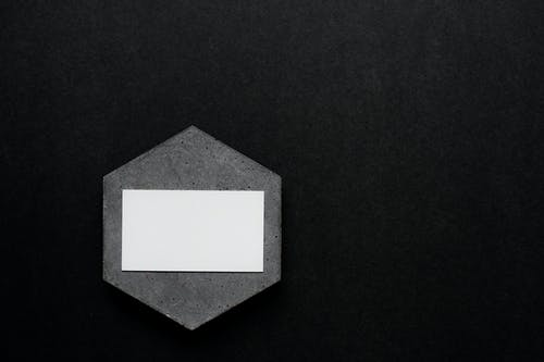 Close-Up Shot of a Business Card on a Black Surface