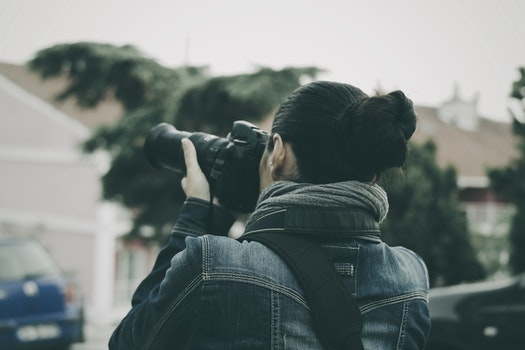 Person Holding Black Dslr Camera Wearing Blue Denim Jacket