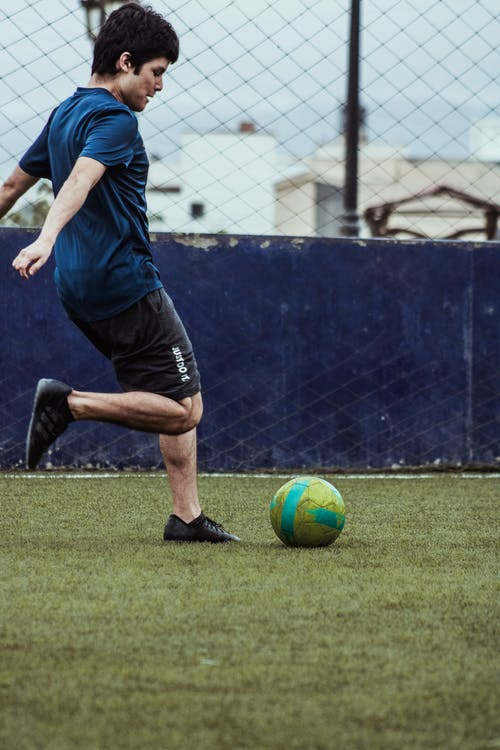 Man in Blue T-shirt and Black Shorts Playing Soccer