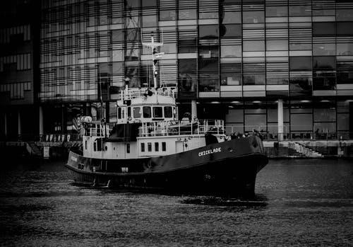 Grayscale Photo of Ship Near Building