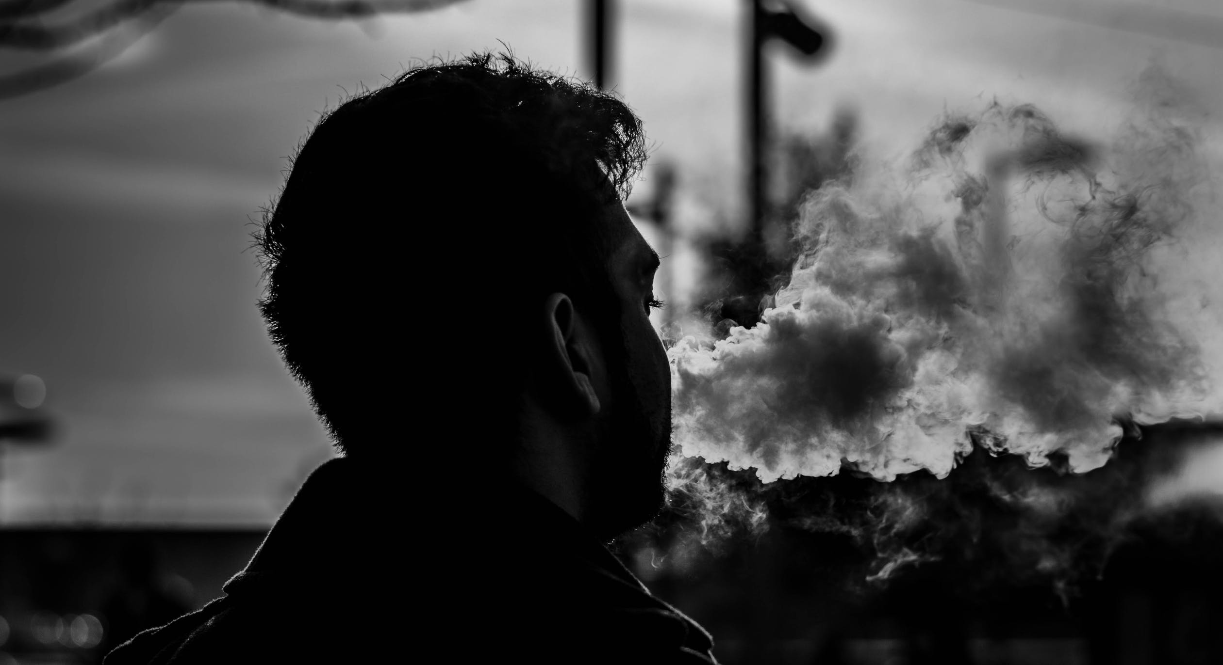 A close-up black and white photo of a young man vaping CBD.