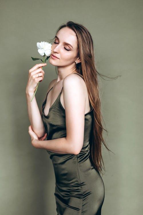 Woman in Green Dress Holding White Flower