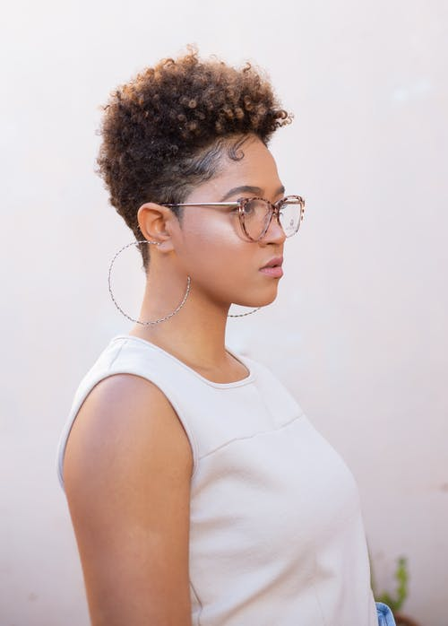Side view of trendy young ethnic woman in eyewear with Afro hairstyle looking forward on light background