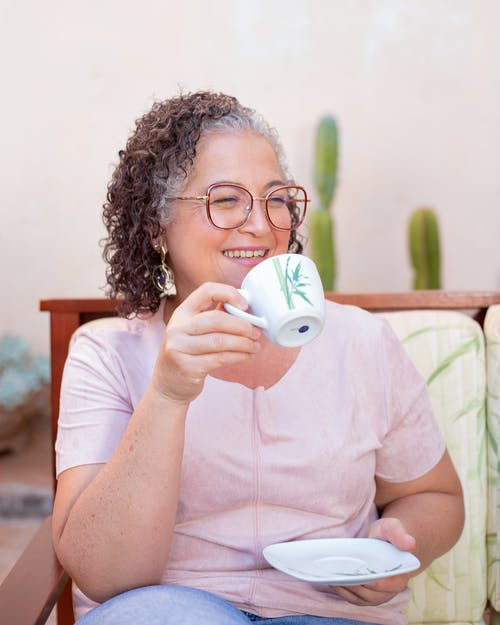 A Woman with Curly Hair Drinking a Cup of Coffee