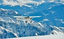 White and Green Monoplane Flying Above Mountains