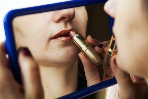 Woman Applying Dark Red Lipstick