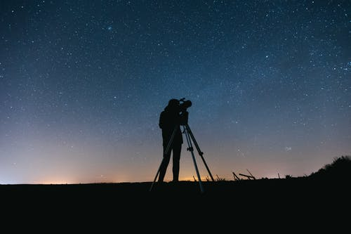 Silhouette of Man Standing on Grass Field Under Starry Night