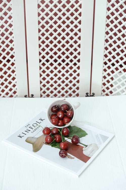 Red Cherries in White Cup on Magazine