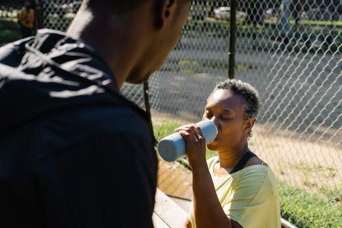 Woman with Her Son Drinking Water from a Jug