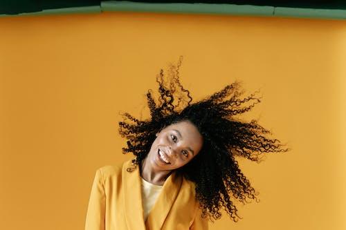 Gratis lagerfoto af flydende hår, gul baggrund, latin kvinde