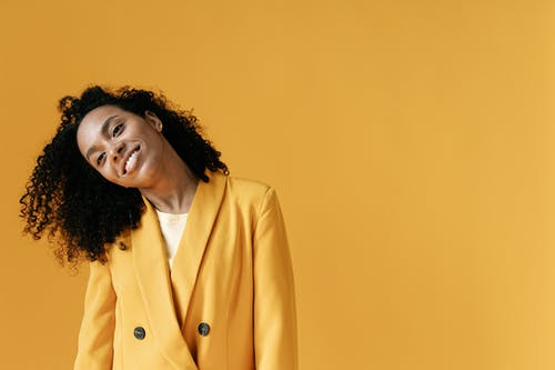 Woman in Yellow Blazer Standing on Yellow Background