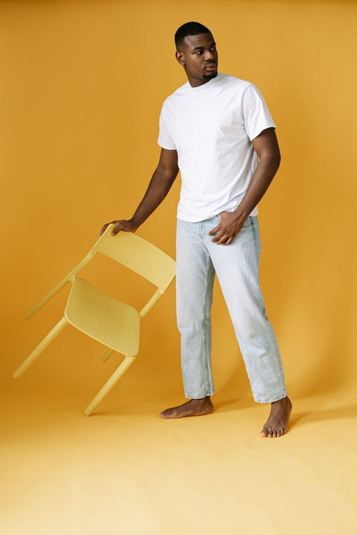 Man Wearing White Shirt Holding a Chair