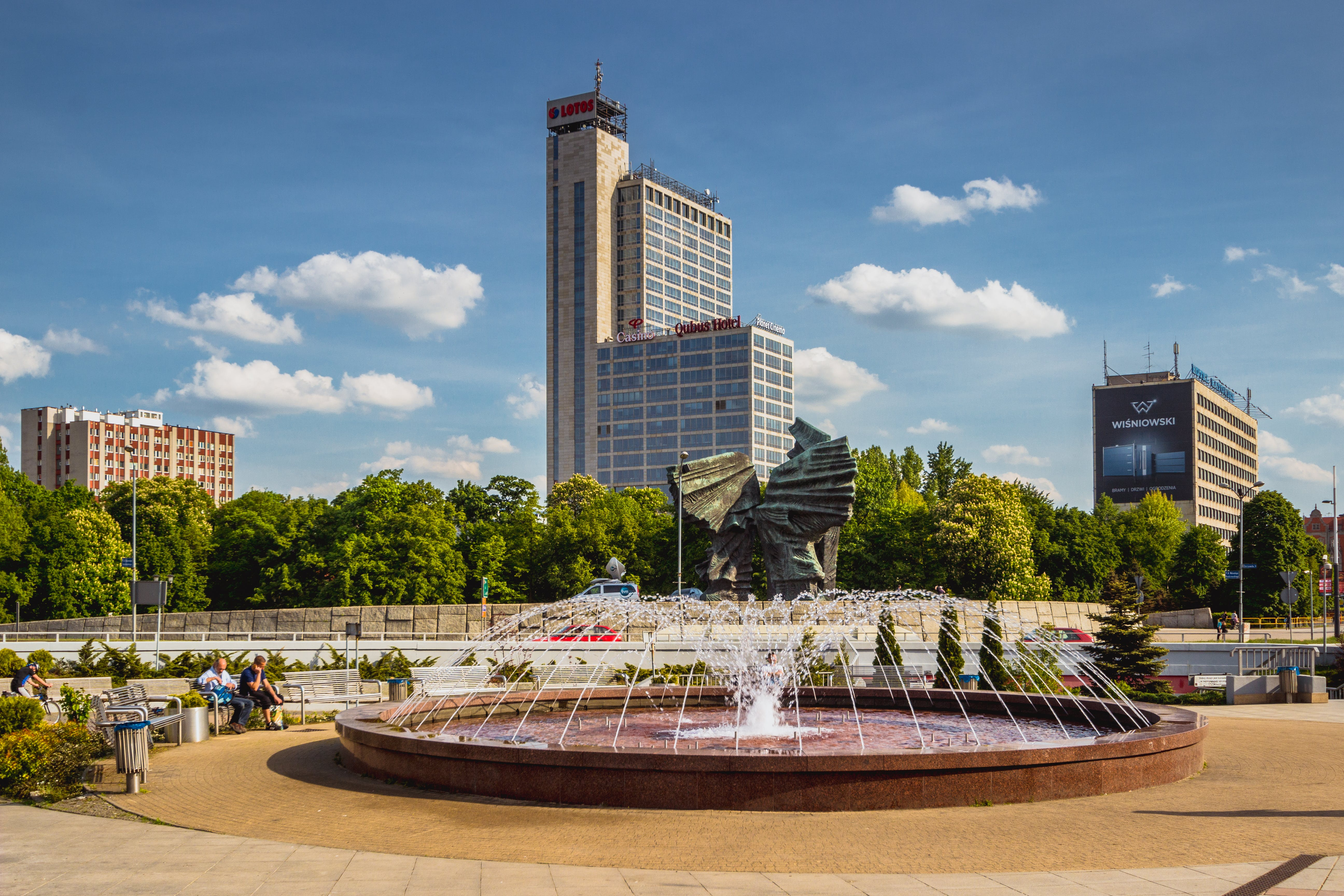 Photography of Two Man Sitting on Bench in Front of Fountain