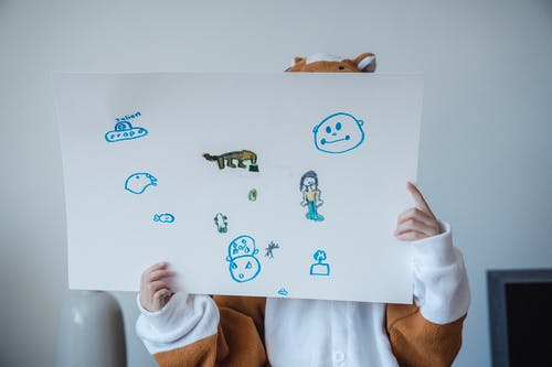 Kid Holding White Paper with Childish Drawings