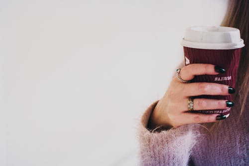 Person With Black Manicured Nails Holding Brown Cup With White Lid