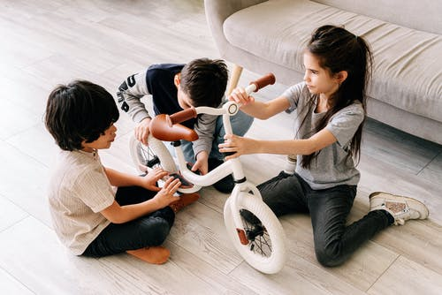 Kids Sitting on the Floor while Playing with a Bike