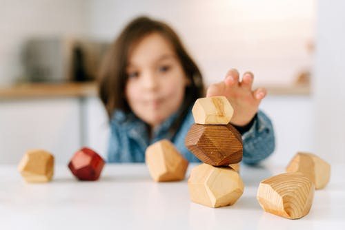 Shallow Focus Photo of a Kid Playing Wooden Blocks