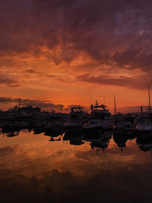 Silhouette of Boats on Water during Golden Hour
