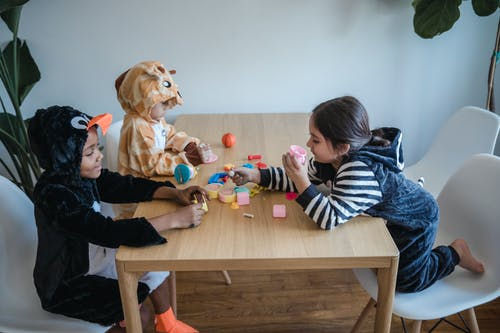 Three Kids in Animal Costumes Playing Toys on a Wooden Table while Sitting